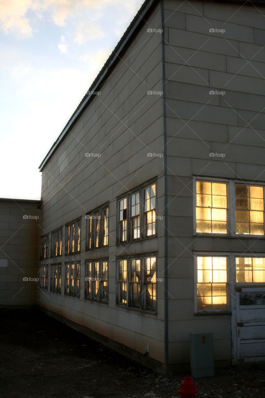 Sun is Flying Low. As the sun begins to end its day, shine a soft golden glow through the windows of an airplane hanger.