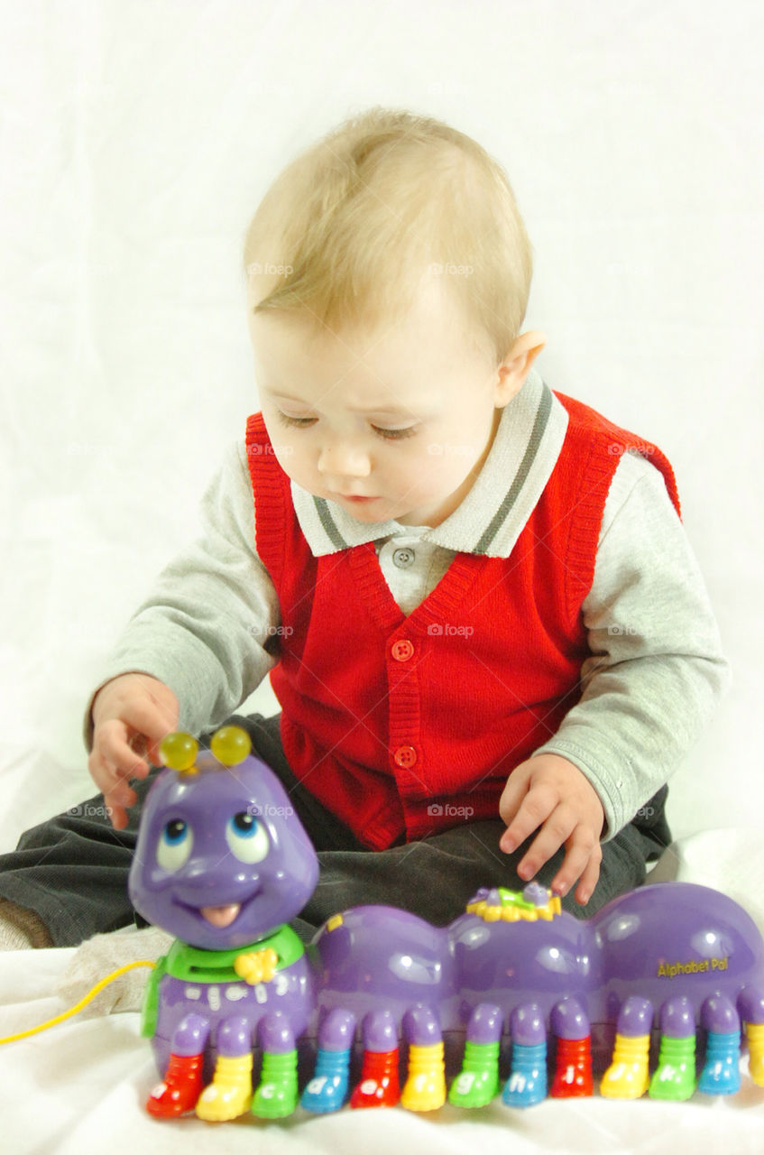 BABY BOY SEATED AND PLAYING WITH A PURPLE SNAKE TOY