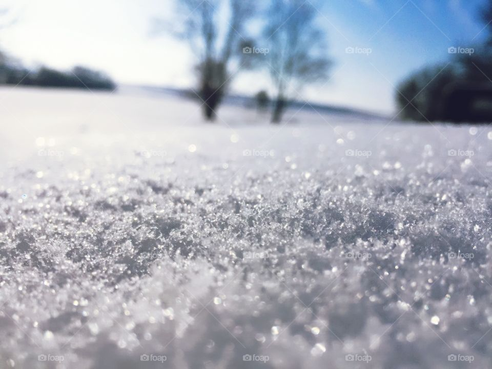 Closeup of snow texture in sunlight, blurred rural background