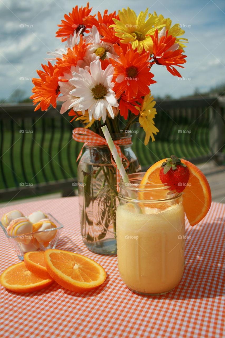 Orange smoothie in jar on table