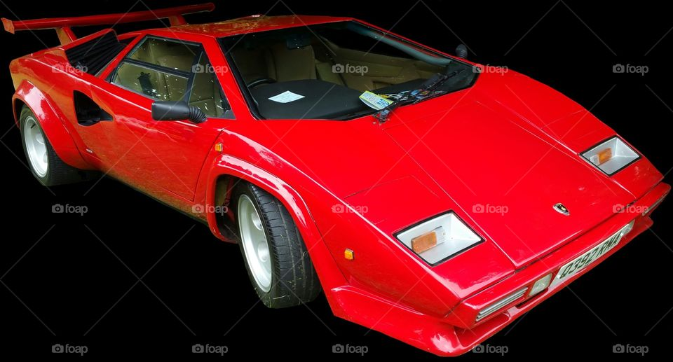 """ISOLATED on BLACK,    Red Lamborghini Countach  it is a mid-engined, V12 sports car produced by Italian car manufacturer Lamborghini from 1974 to 1990. Its design pioneered and popularized the wedge-shaped, sharply angled look popular in many high-performance sports cars. It also popularized the """"cab forward"""" design concept, which pushes the passenger compartment forward to accommodate a larger engine.  In 2004, American car magazine Sports Car International named the car number three on the list of Top Sports Cars of the 1970s, and listed it number ten on their list of Top Sports Cars of the 1980s.  Engine   The rear wheels were driven by a traditional Lamborghini V12 engine mounted longitudinally with a mid-engined configuration. This contrasted with the Miura with its centrally mounted, transversely-installed engine. For better weight distribution, the engine is pointed """"backwards""""; the output shaft is at the front, and the gearbox is in front of the engine, the driveshaft running back through the engine's sump to a differential at the rear. Although originally planned as a 5 L (310 cu in) powerplant, the first production cars used the Lamborghini Miura's 4-liter engine. Later advances increased the displacement to 4754 cc and then (in the """"Quattrovalvole"""" model) 5167 cc with four valves per cylinder.  All Lamborghini Countaches were equipped with six Weber carburetors until the arrival of the 5000QV model, at which time the car became available in America, and used Bosch K-Jetronic fuel injection. The European models, however, continued to use the carburetors (producing more power than fuel-injected cars) until the arrival of the Lamborghini Diablo, which replaced the Countach."""