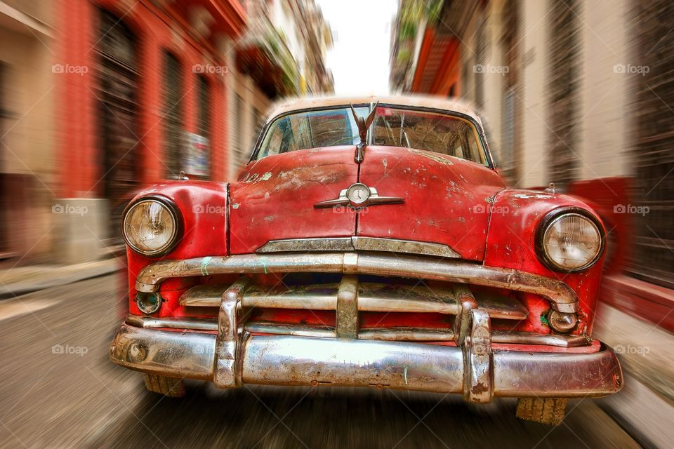 Red car racing in Havana, Cuba. Classic American car in Havana, Cuba with appearance of speeding in the narrow street and matching color buildings.