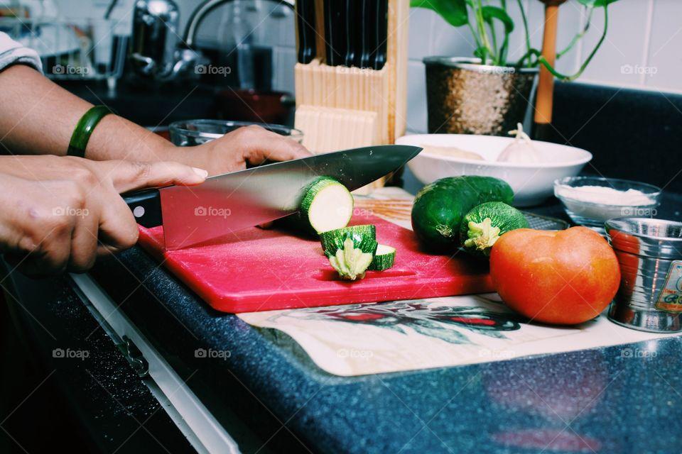 Young woman working in kitchen cutting zucchini