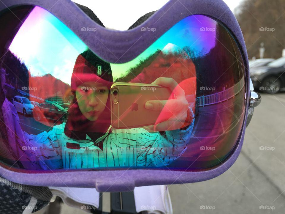 Woman taking selfie reflecting in ski goggles