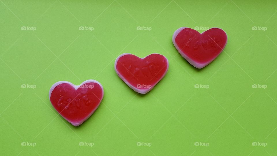Three red candy hearts on bright green background