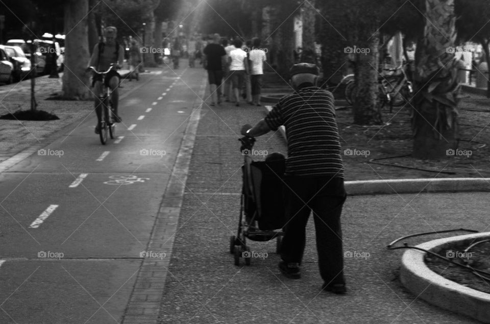Old man walking around with a stroller