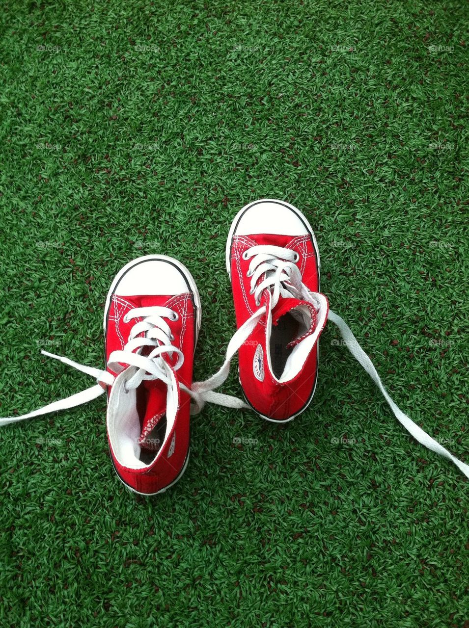 Baby red shoes with green background