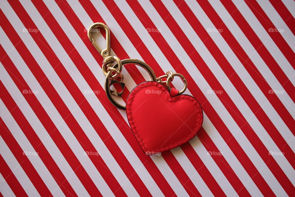 Heart-shaped key ring on red and white stripes flat lay.