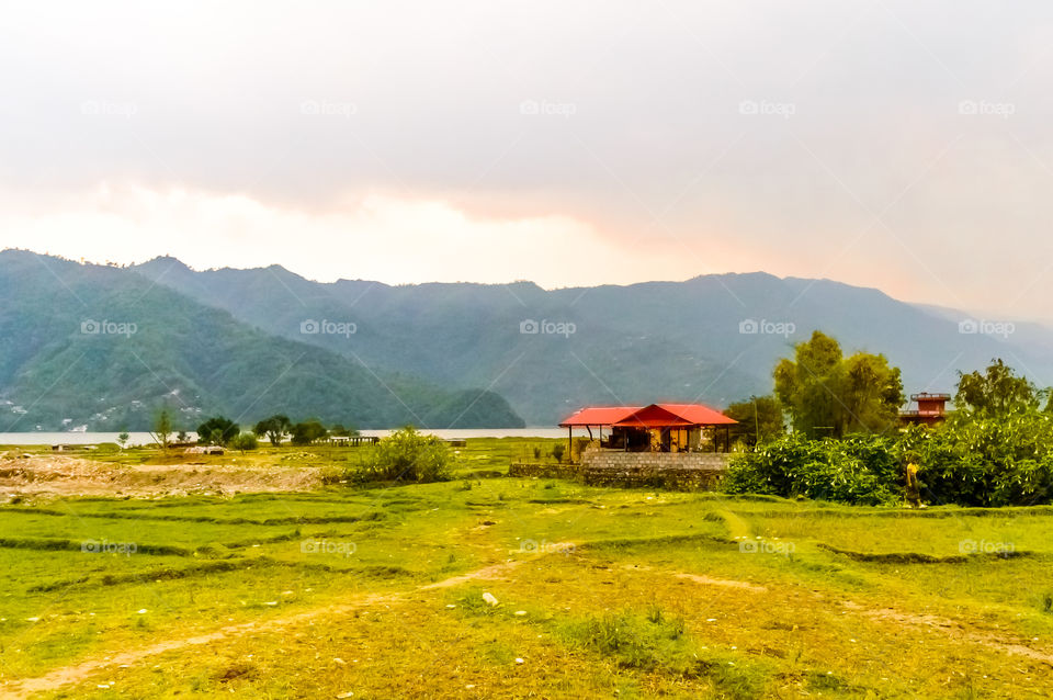 Photograph of winter season: A farm house, lake, mountain, clear sky and farm land. Wide angle landscape of Pokhara Lake at Kathmandu Nepal. Vintage film look. Vacation Freedom, Simplicity Concept.