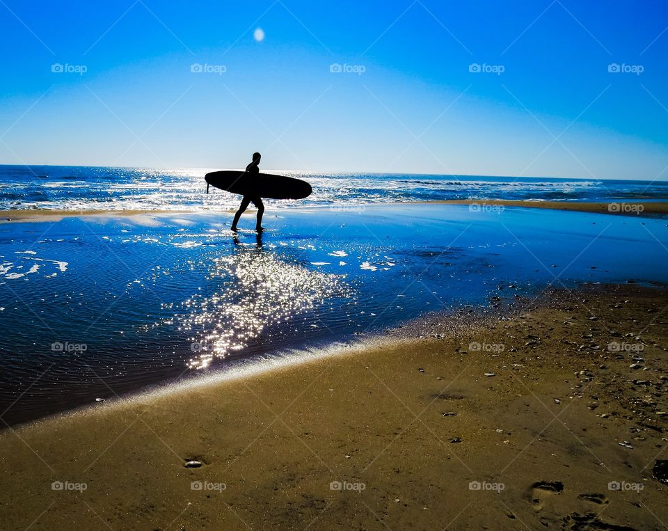Surfer silhouette at sunset.