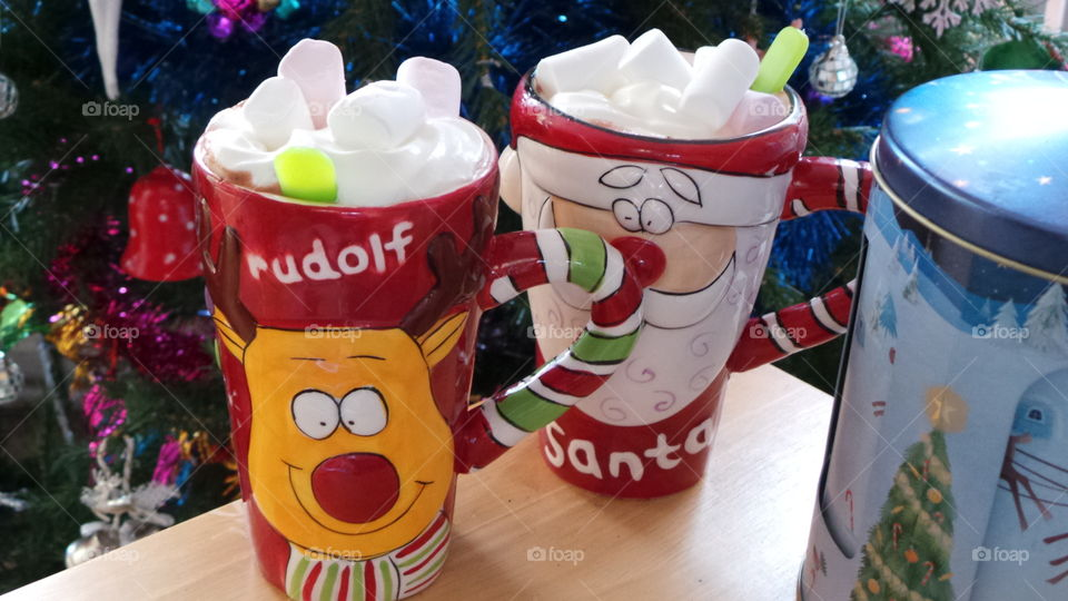 festive hot chocolates in Christmas mugs by the Christmas tree