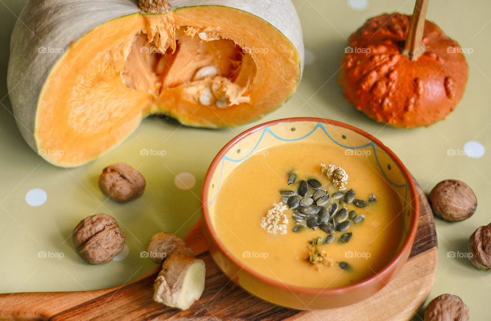 Autumn mood at home. Pumpkin soup with ginger, seeds, walnuts on cutting board and pumpkins on the table.
