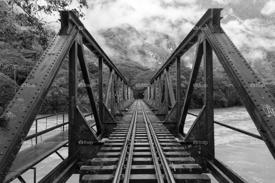 Railroad bridge over river. Metal railroad bridge over wide river. Railroad tracks disappear to horizon. Misty mountains in the background