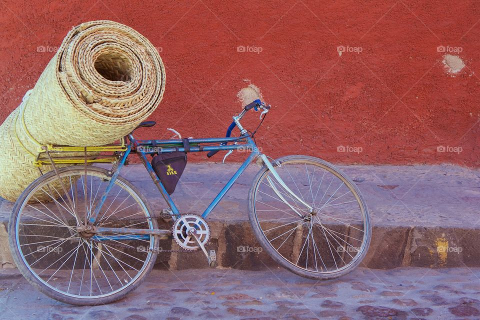A bicycle is parked on a cobble stone street leaning on the straw mat cargo,