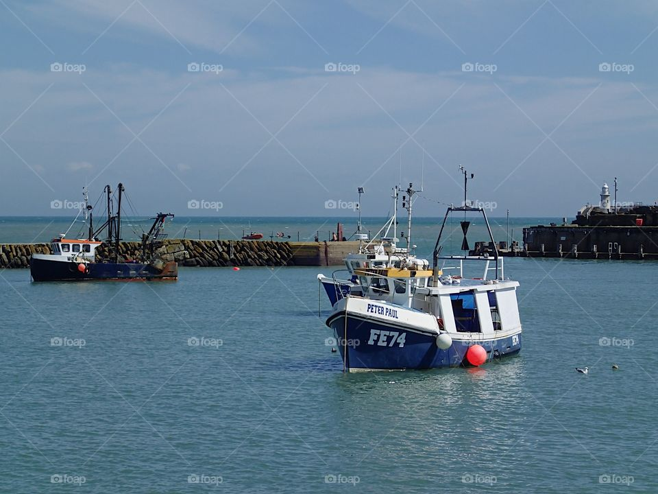 A bright blue fishing boat anchored in the harbor in Folkestone, England on a sunny summer day.