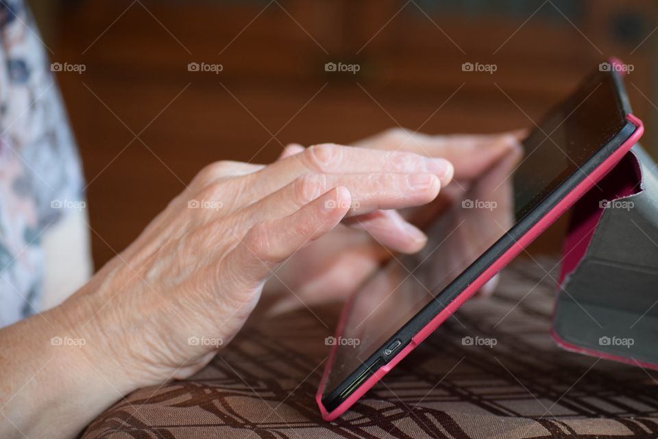 A Grandmother keeps in touch with family using modern technology.
