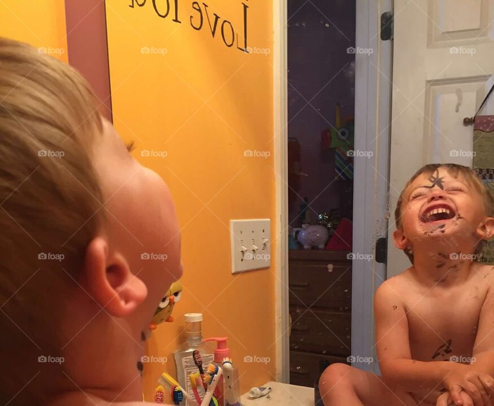 Toddler boy laughing at the drawings he put all over his face.
