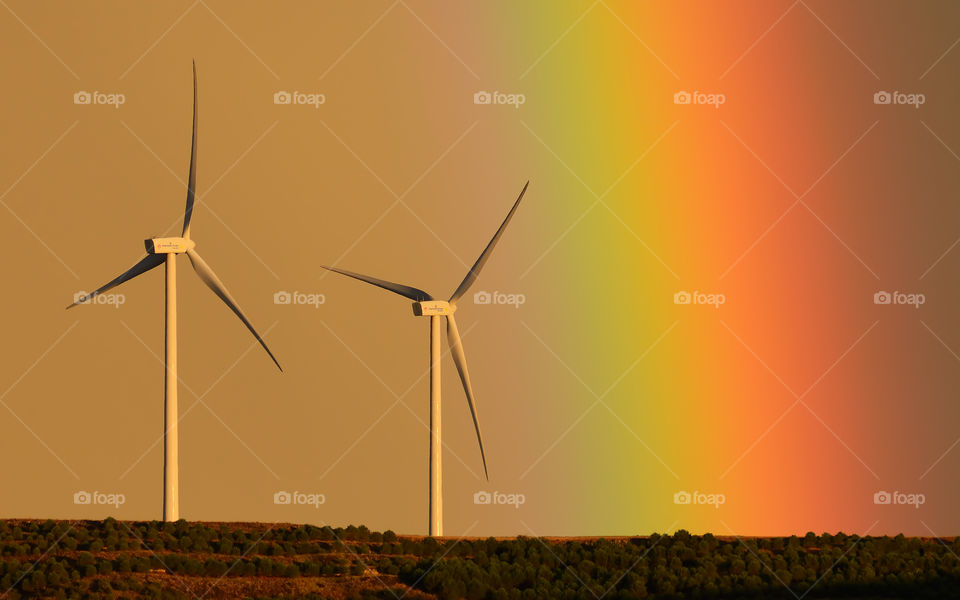 Wind towers at sunset and rainbow