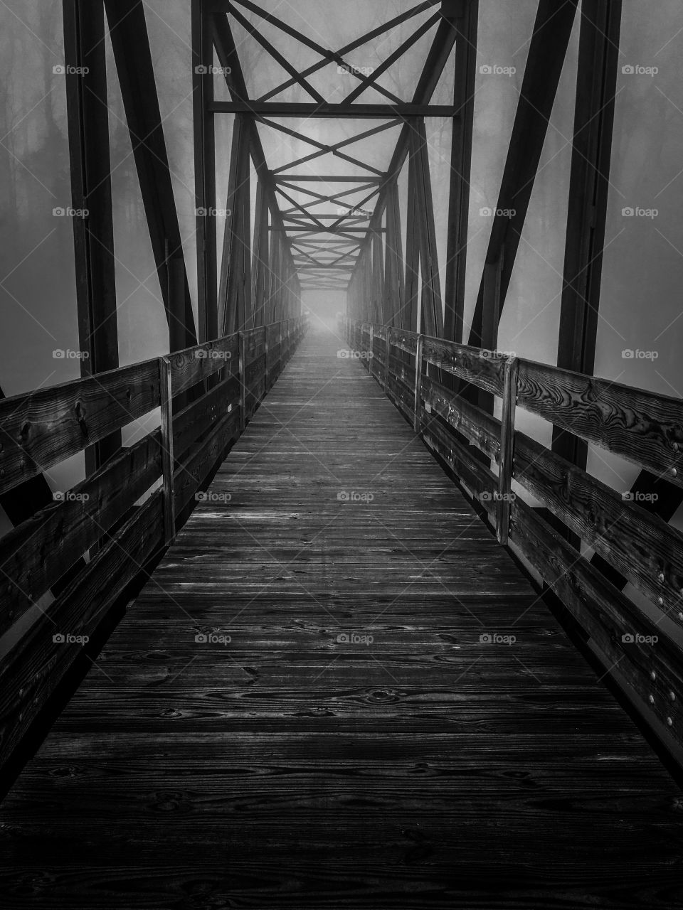Black and white of an old steel and wood truss footbridge across the lake at Tims Ford State Park in Winchester Tennessee. The dark and foggy ambiance gives it a haunting and mysterious feel.