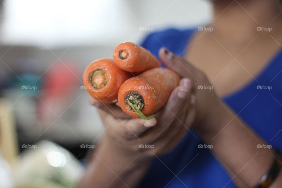 Close-up of woman holding carrots