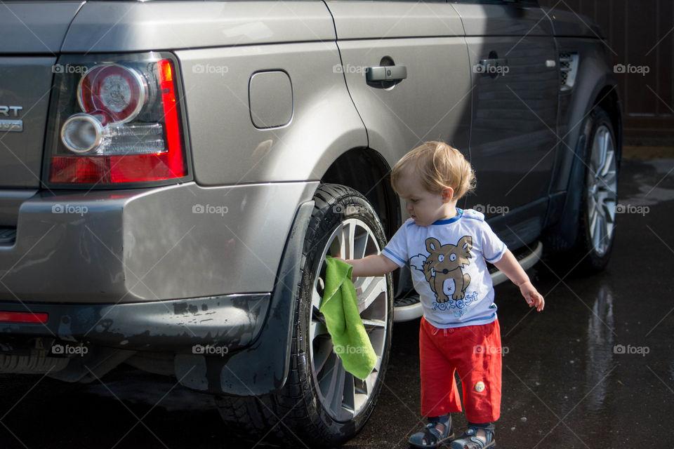 Cute little boy cleaning car wheel with cloth