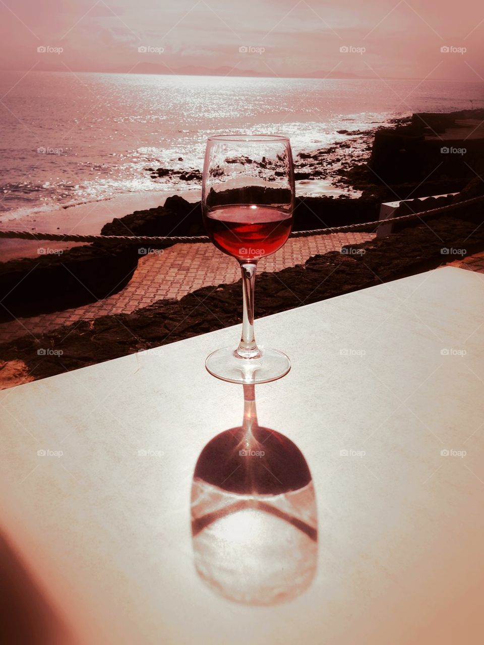 Reflection of red wine glass on table near the beach