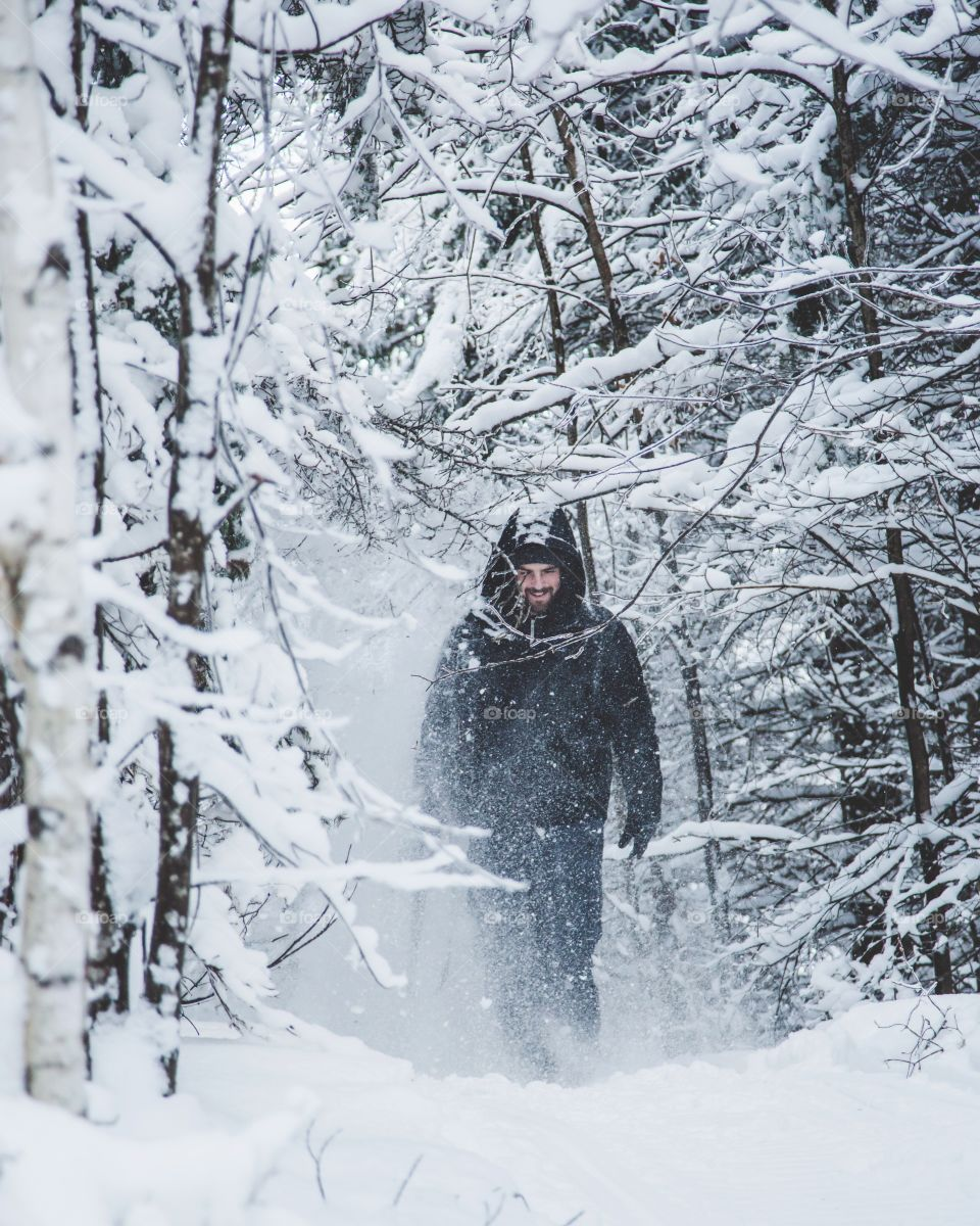 A young man walking through a snowy forest, exploring