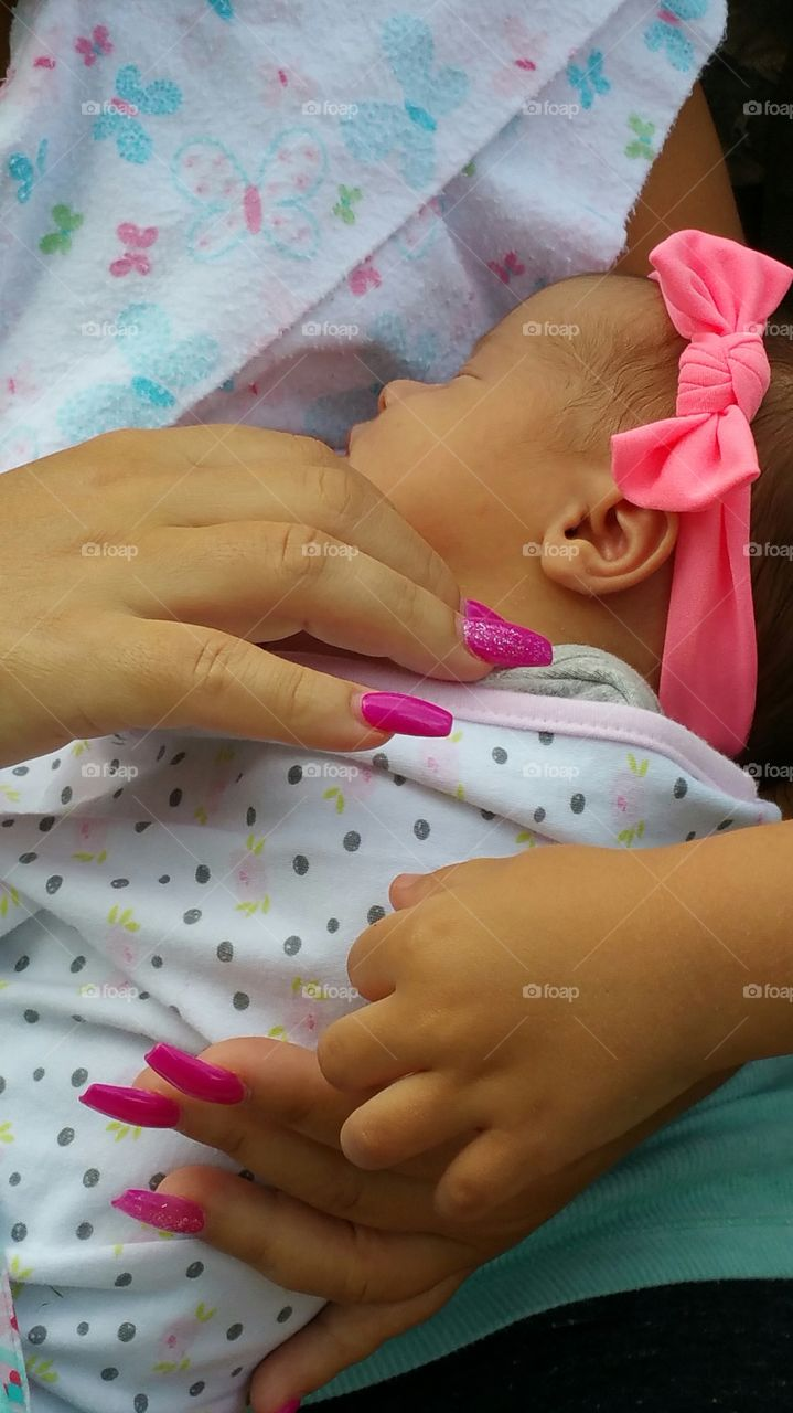 Hands touching newborn baby