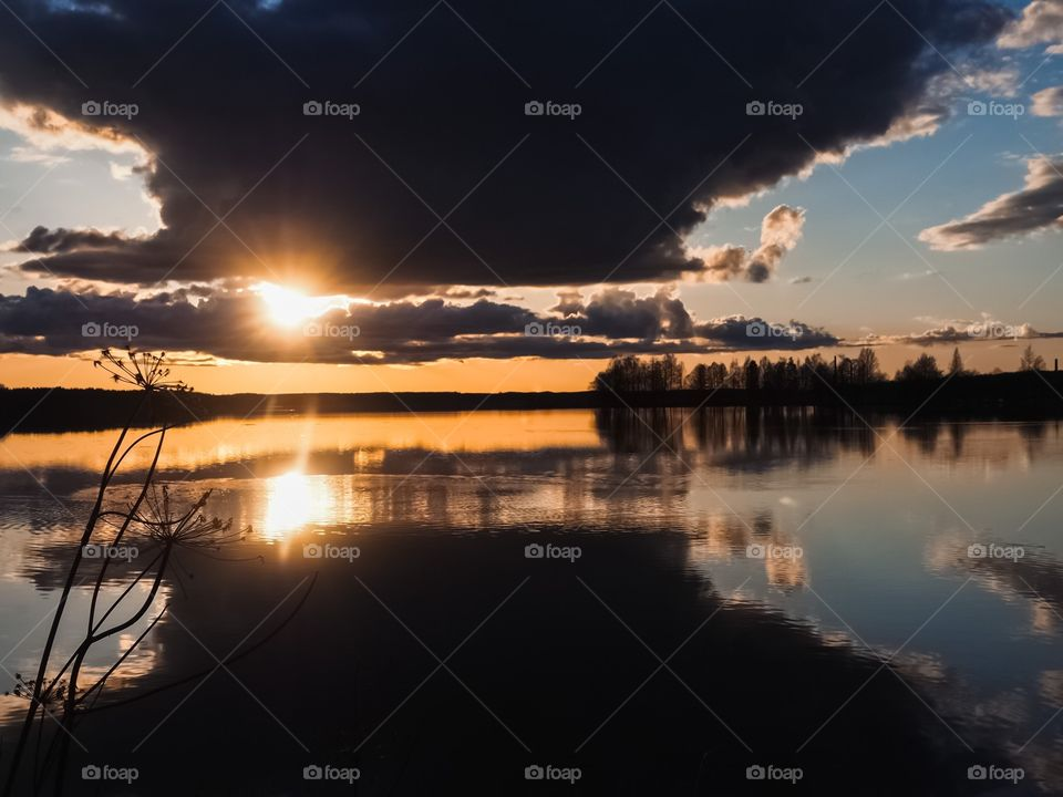 The Sun shines through the clouds. Beautiful lakescape scenery.