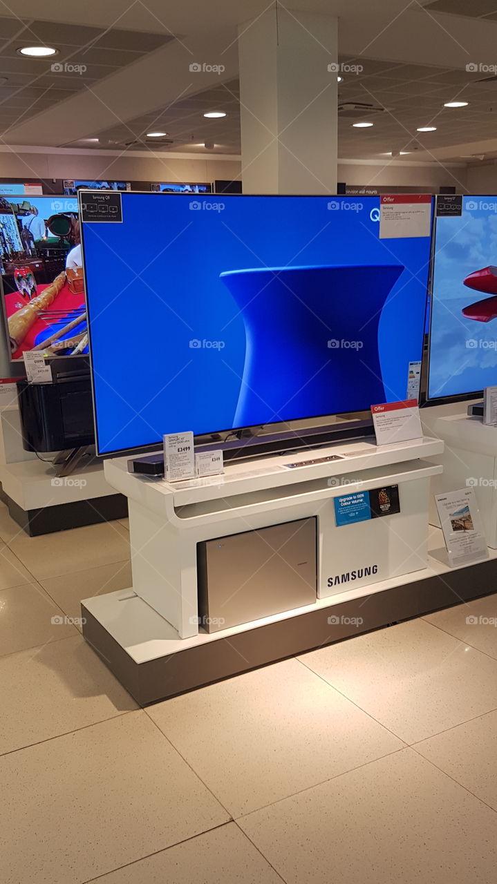 Samsung QLED television 4K Ultra High Definition TV with soundbar and sub-woofer on plinth