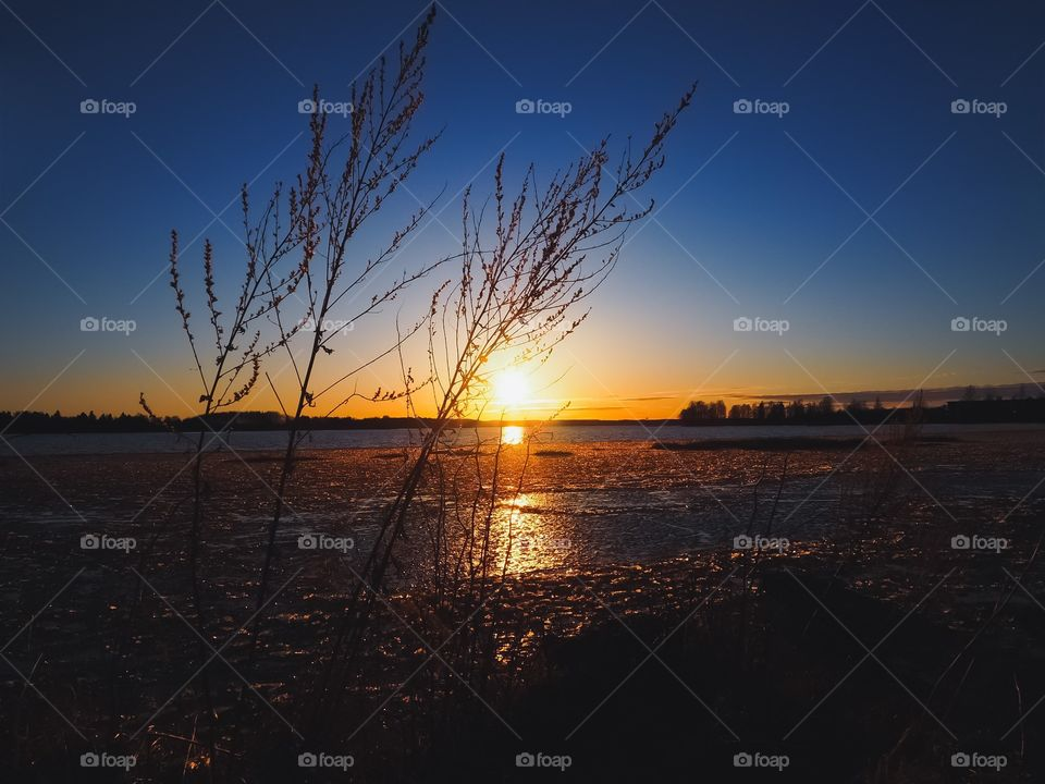 Beautiful evening sky. Sunset colors in the sky and icy water. Hay in front of the view.