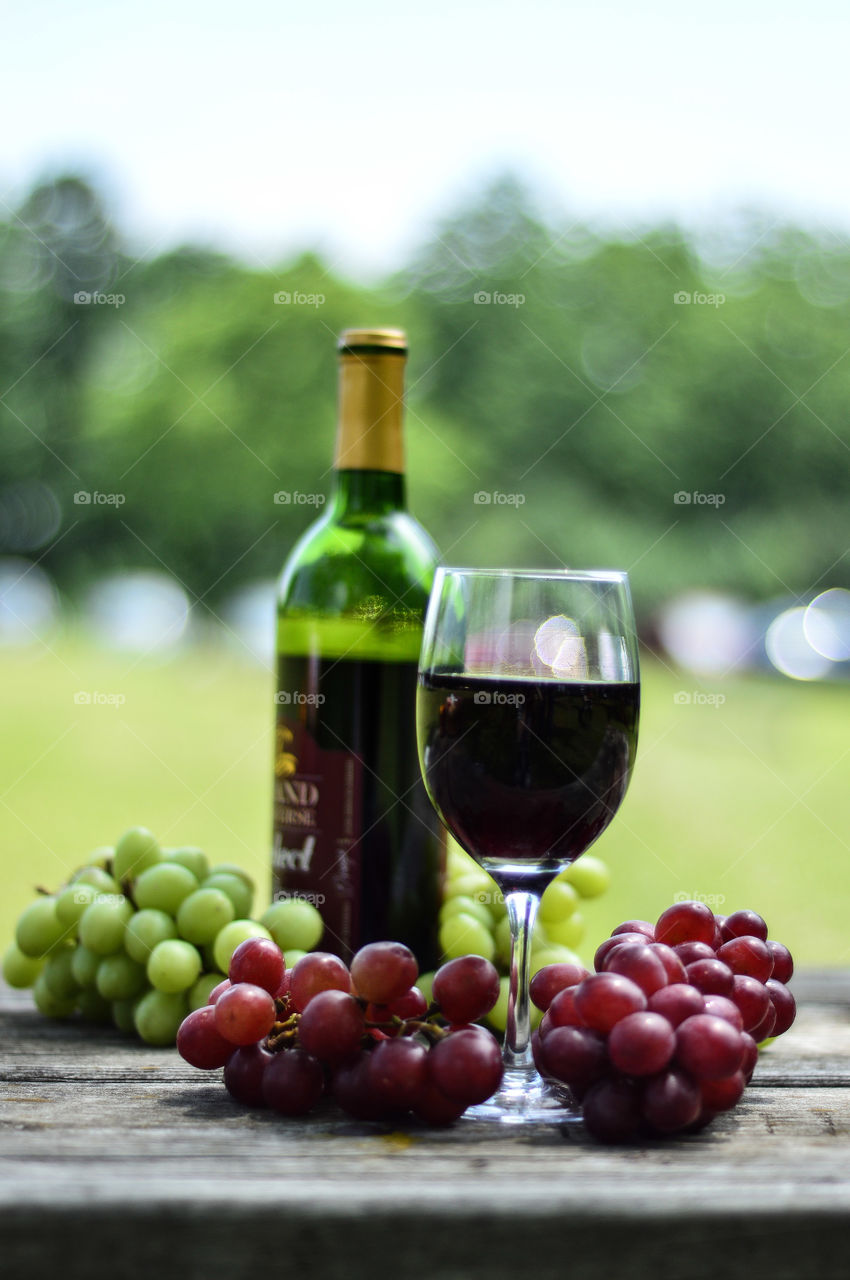 red wine. red and green grapes surround the red wine on  wooden a  table with wine bottle in the background