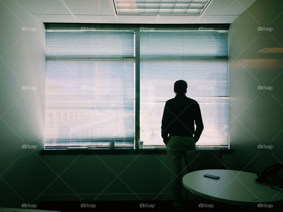 Man standing in his office cabin and thinking