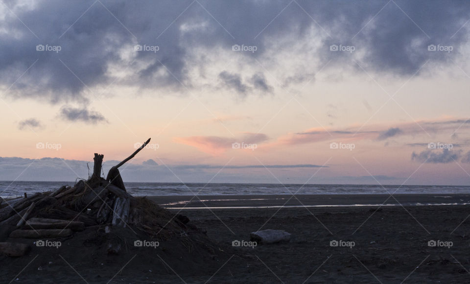 A half buried beach fort on City Beach at sunset in Ocean Shores.