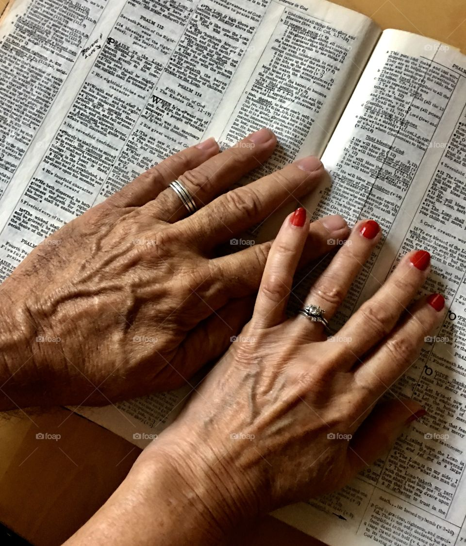 Hands of husband and wife on a Bible