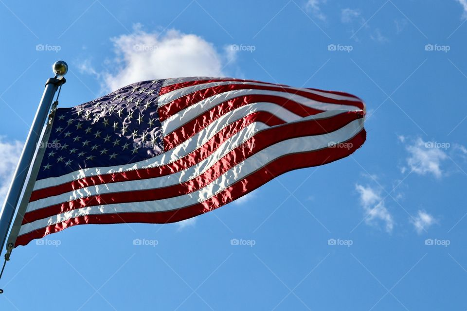American flag closeup on flagpole flying, rippling in the wind, on vivid clear blue sunny sky closeup