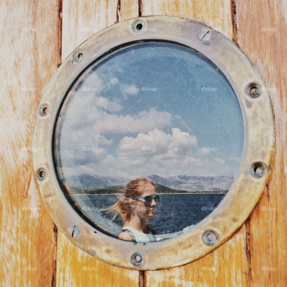 Girl reflected in ferry porthole