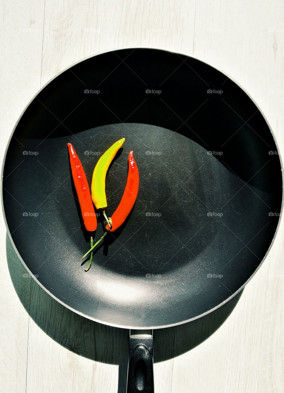 red and yellow chilli on dark frying pan with light wooden background