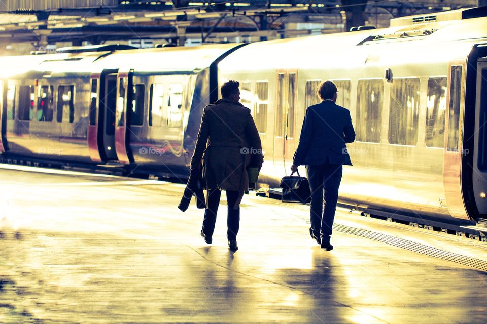 A pair of businessmen commuting at a railway station and walking along a sunlit platform before boarding a waiting train.