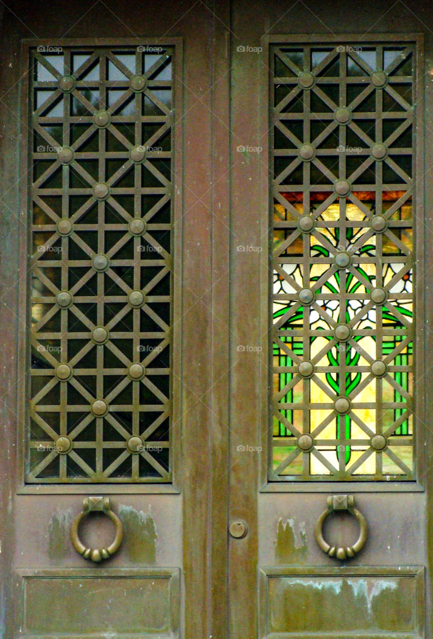 A beautiful stained glass window can be seen through the doors of a mausoleum.