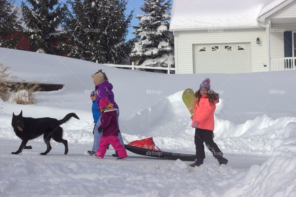 Family with their pet walking in snow