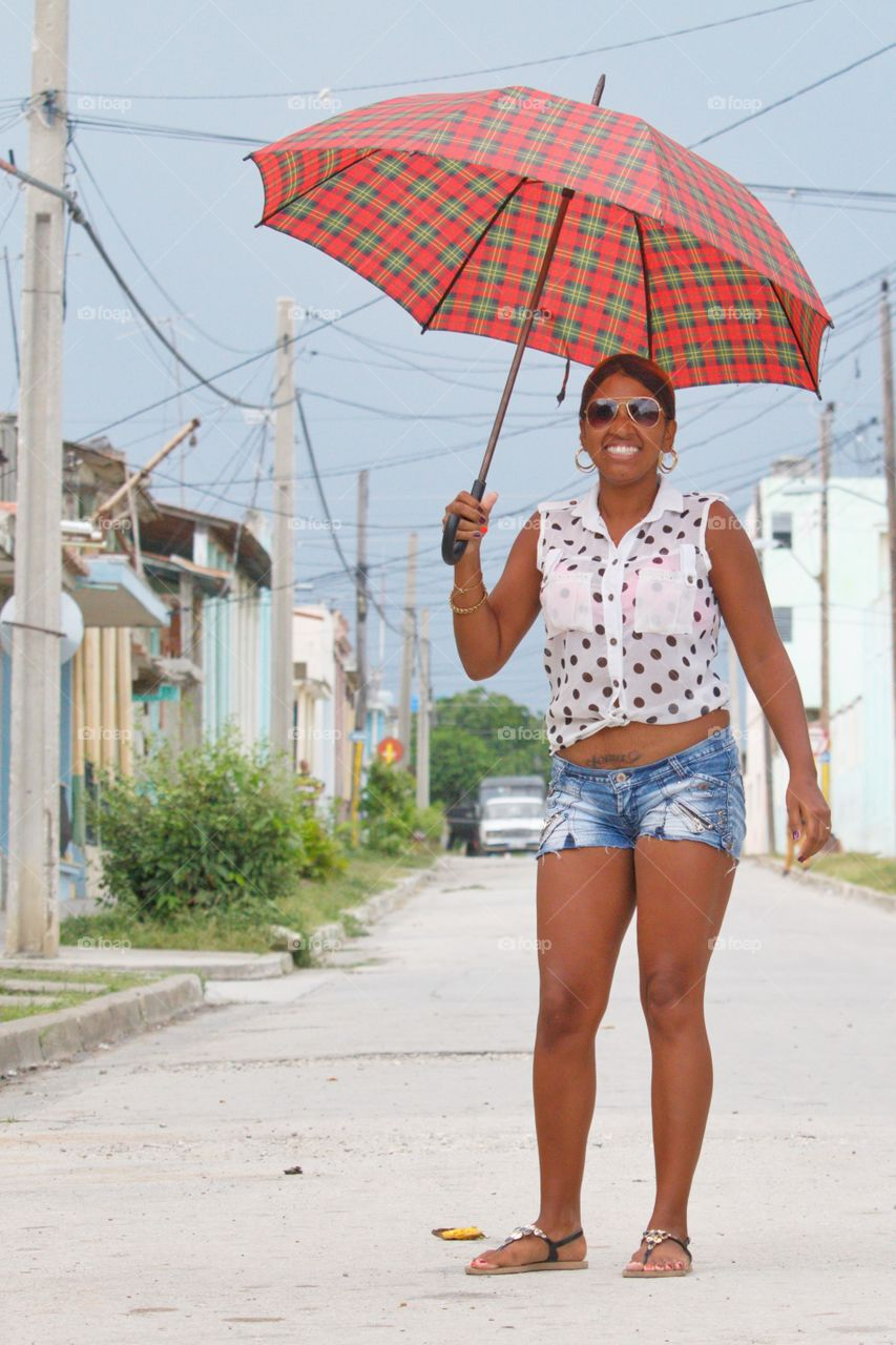 Smiling woman holding umbrella in city