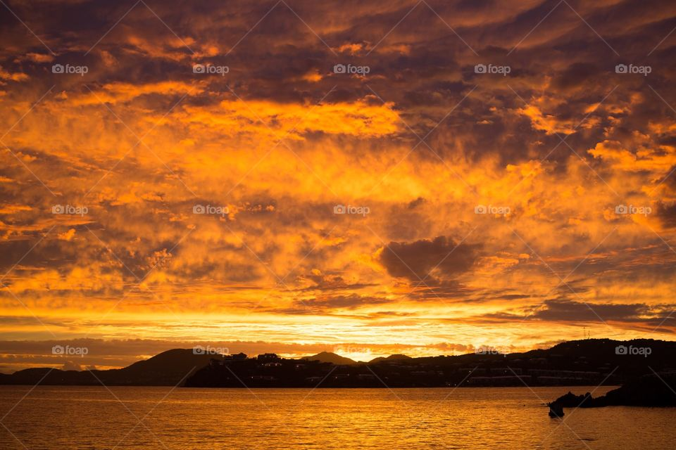 Sunset over mountainous caribbean island from the water