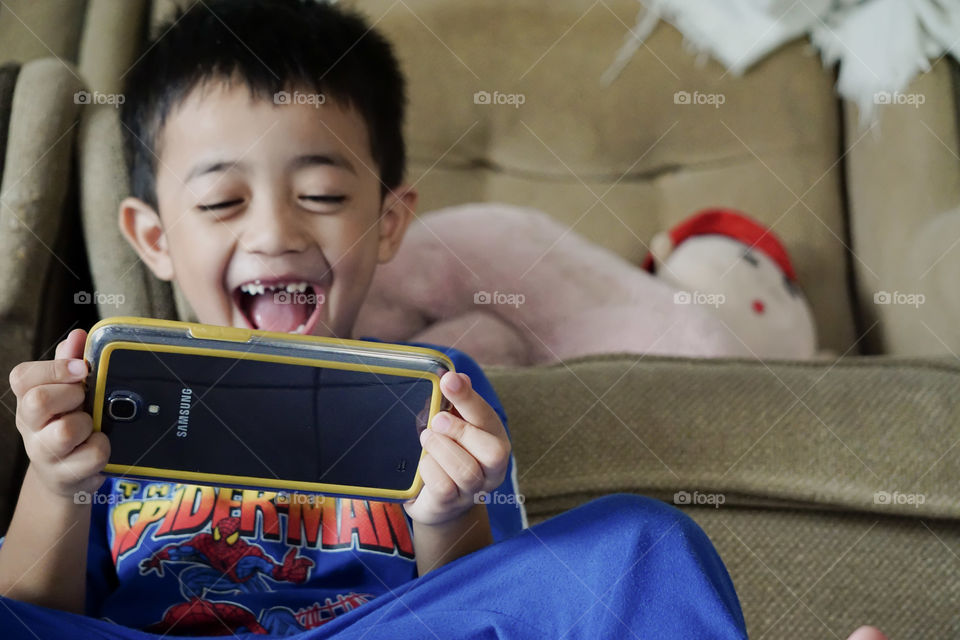 A boy laughing with his mobile phone