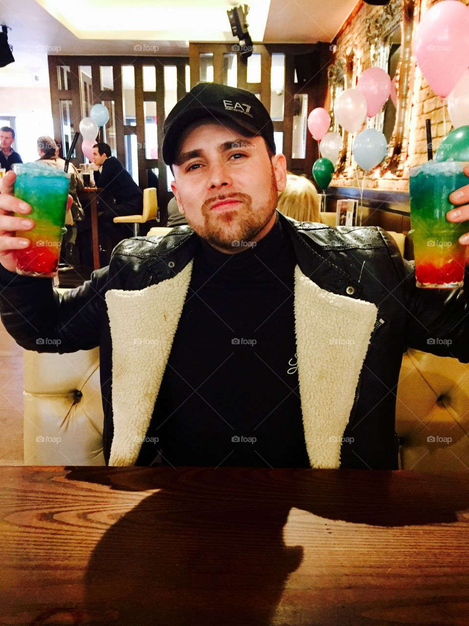 Gay pride photo of a male drinking two rainbow cocktails with pink and blue balloons
