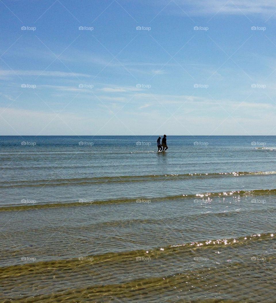 Two people walking in sea