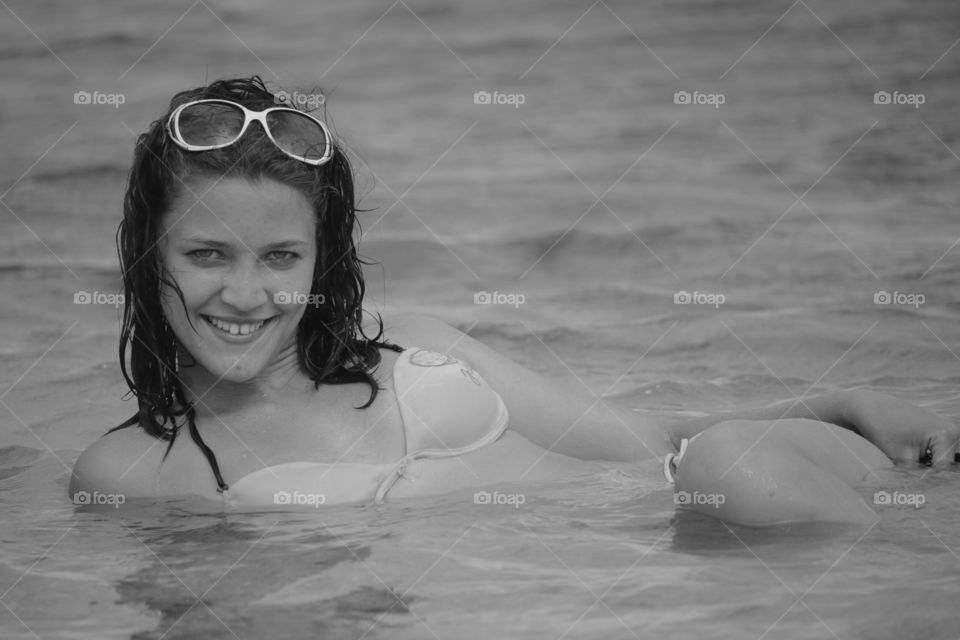 Happy woman lying in sea