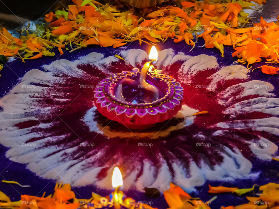 Colourful diya or oil lamp with design which is put on Rangoli and flower petals design. It is used in Indias biggest festival DIWALI for decoration. looking attractive.