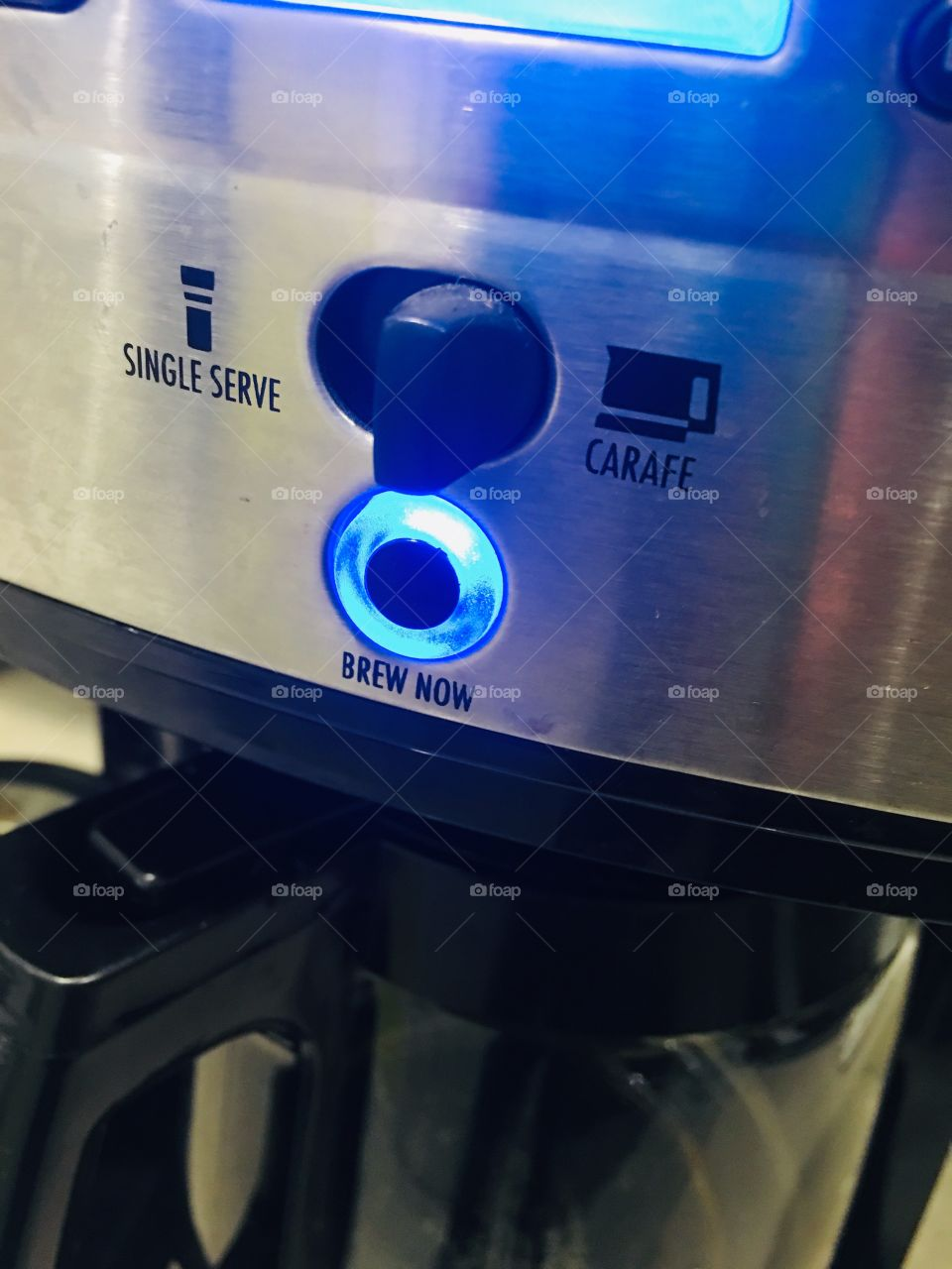 """Coffee machine with a bright blue """"brew now"""" light on"""