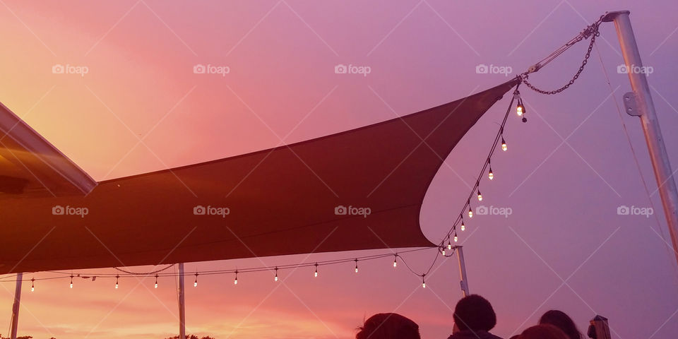 Awning with Edison lights strung over a bar deck at Beach restaurant in NC. sunset silhouette